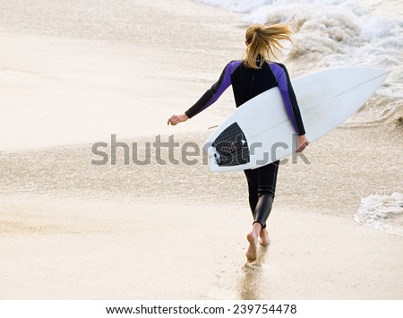 Rear view of beautiful sexy young woman surfer girl in bikini with white surfboard - stock photo