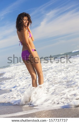 Rear view of beautiful young woman in bikini standing in the surf waves on a deserted tropical beach with blue sky
