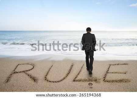 Rear view of black suit businessman standing with rule word written on sand beach background - stock photo