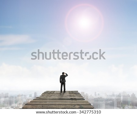 Rear view of black suit man standing gazing on wooden bridge, with sunny sky clouds cityscape background.