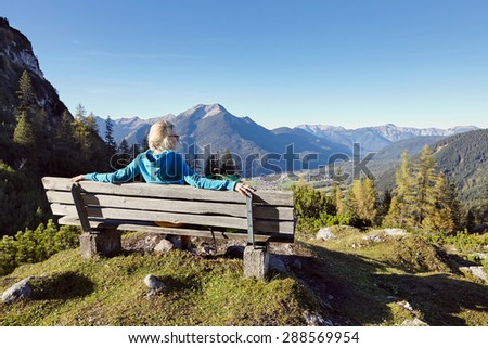 Rear view of blonde female hiker resting on wooden bench with view at beautiful mountain landscape - stock photo