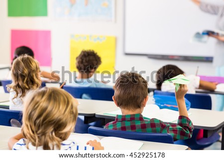 Rear view of boy holding paper airplane in classroom