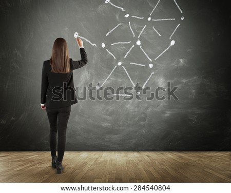 Rear View of Brunette Business Woman Drawing Connected Lines on Chalkboard in Connectivity, Communication and Network Concept Image - stock photo