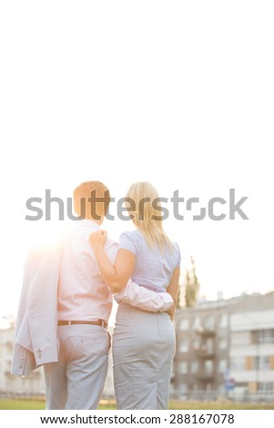 Rear view of business couple standing with arms around against clear sky on sunny day - stock photo