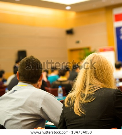Rear view of business people listening attentively at conference. - stock photo