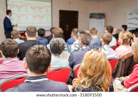 Rear view of business people listening attentively at conference. Presenter with report near the screen. - stock photo