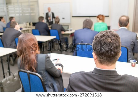 Rear view of business people listening attentively while sitting at the classroom - stock photo