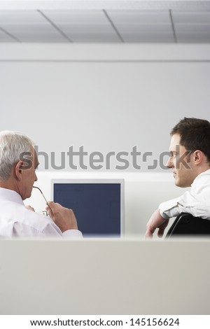 Rear view of business people sitting at computer desk in office cubicle - stock photo