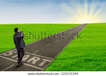 Rear view of business person carrying briefcase walk on the road to start his journey for success - stock photo