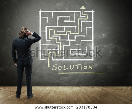 Rear View of Business Person Scratching Head with Hand in Confusion Standing in front of Chalkboard with Drawing of Maze with Solution in Business Concept Image - stock photo