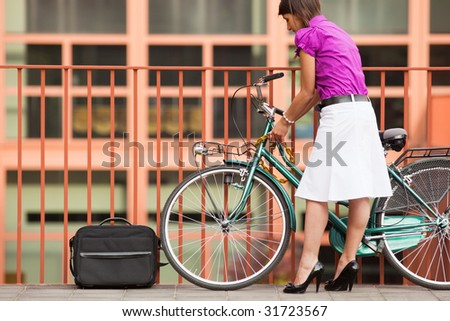 rear view of business woman locking padlock to her bike. Copy space