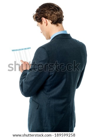 Rear view of businessman analyzing annual report - stock photo