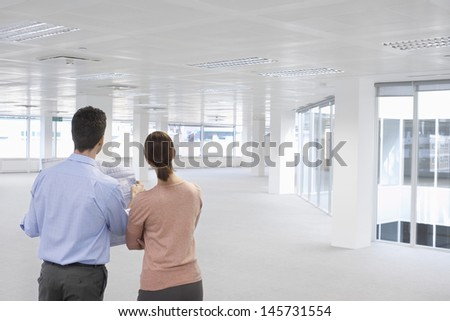 Rear view of businessman and businesswoman looking at plan and empty office space - stock photo