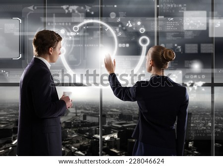 Rear view of businessman and businesswoman touching icon of digital screen - stock photo