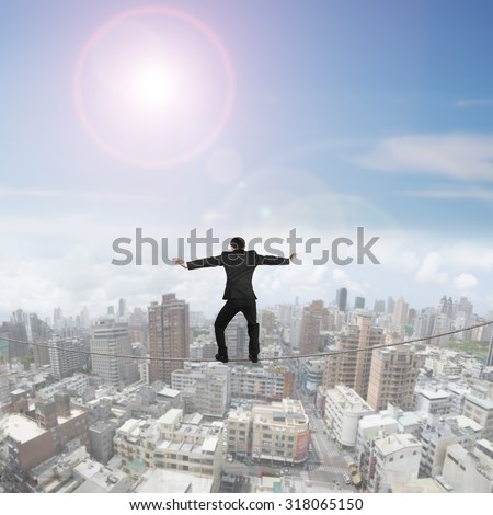Rear view of businessman balancing on tightrope, with sunny sky cityscape background. - stock photo