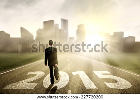 Rear view of businessman carrying briefcase and walking on the road towards future 2015 - stock photo