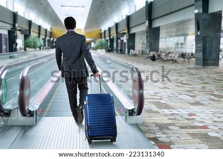 Rear view of businessman carrying luggage walk toward escalator in airport hall - stock photo
