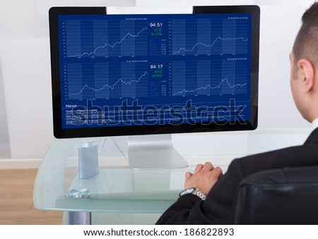 Rear view of businessman checking the stock market on computer in office
