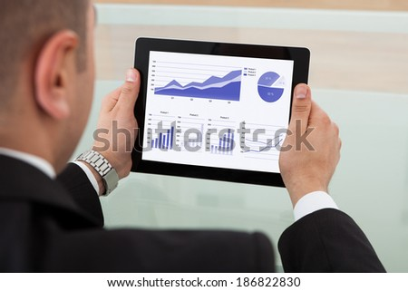 Rear view of businessman checking the stock market on digital tablet in office - stock photo