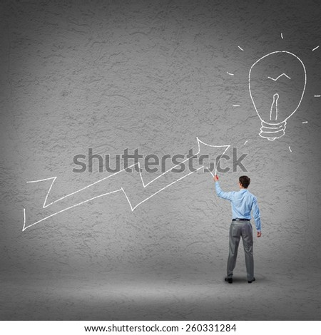 Rear view of businessman drawing increasing graph - stock photo