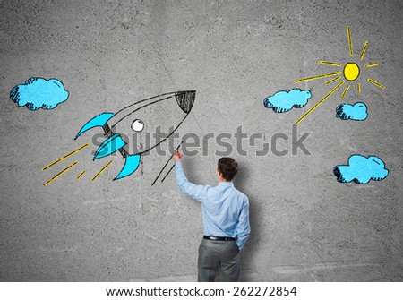 Rear view of businessman drawing rocket on wall - stock photo