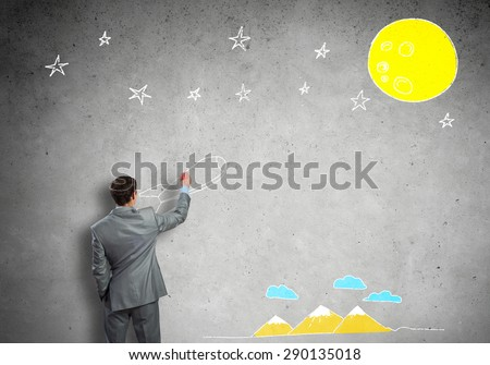 Rear view of businessman drawing rocket on wall
