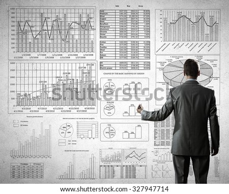 Rear view of businessman drawing with marker business sketches on wall - stock photo