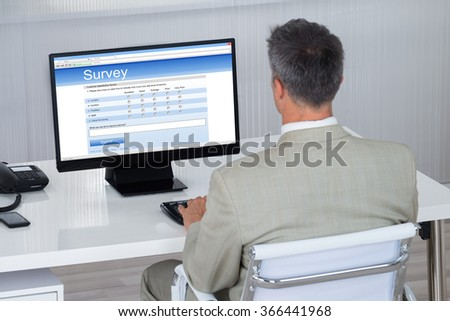 Rear view of businessman filling survey form on computer at desk in office - stock photo