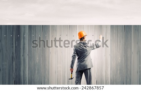 Rear view of businessman fixing white blank banner with hammer