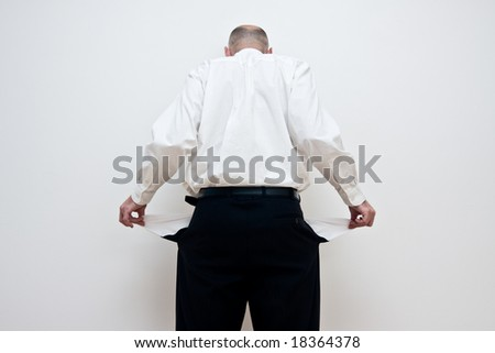 Rear view of businessman holding out pockets to show they are empty, white background.