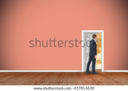 Rear view of businessman in suit gesturing against open door on green wall - stock photo
