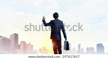 Rear view of businessman look at sunrise above city