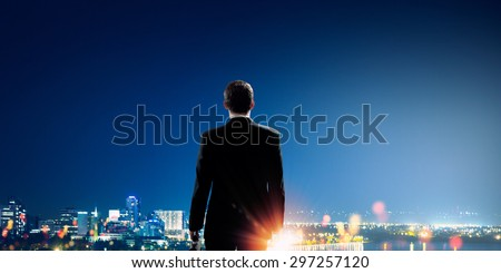 Rear view of businessman looking at night city - stock photo