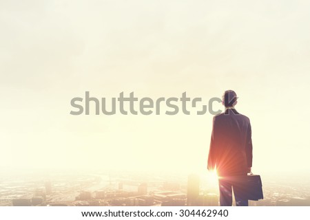 Rear view of businessman looking at sunset above city - stock photo