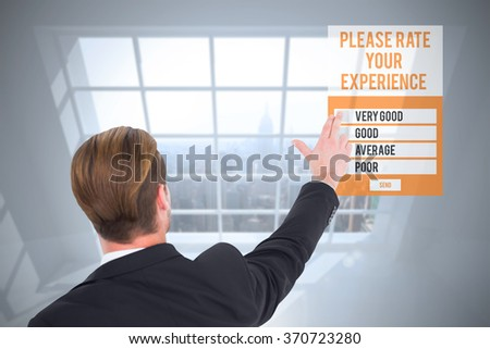 Rear view of businessman pointing with his fingers against room with large window showing city - stock photo