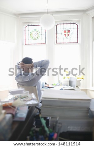 Rear view of businessman relaxing at desk in home office - stock photo