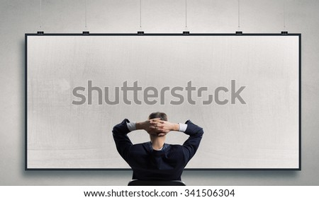 Rear view of businessman sitting on chair with hands on head - stock photo