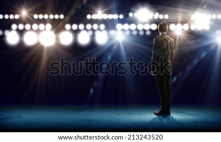 Rear view of businessman standing in lights of stage - stock photo
