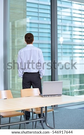 Rear view of businessman standing in office with hands in pockets