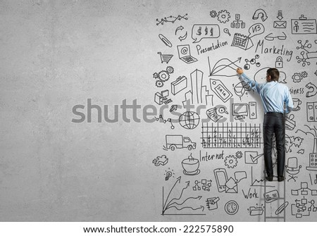 Rear view of businessman standing on ladder and drawing business ideas - stock photo