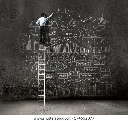 Rear view of businessman standing on ladder and drawing business sketch on wall