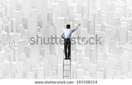 Rear view of businessman standing on ladder and drawing project