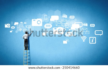 Rear view of businessman standing on ladder and reaching cloud - stock photo