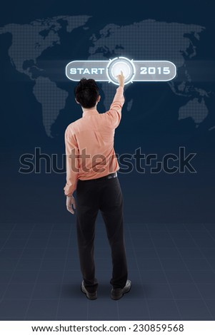 Rear view of businessman touching a virtual button to start his business in 2015 - stock photo