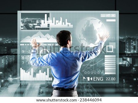 Rear view of businessman touching icon of media screen - stock photo