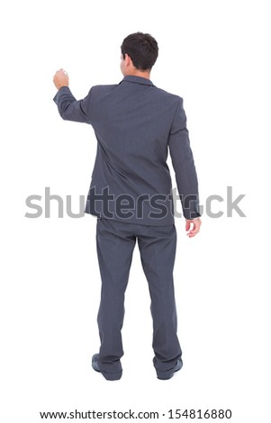 Rear view of businessman using a marker on white background