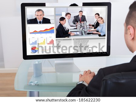 Rear view of businessman video conferencing with team on computer in office - stock photo