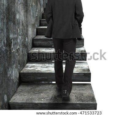 Rear view of businessman walking up the old concrete stairs, isolated on white background.