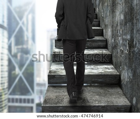 Rear view of businessman walking up the old concrete stairs, with city buildings background.
