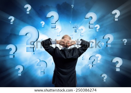Rear view of businessman with arms on head thinking something over - stock photo